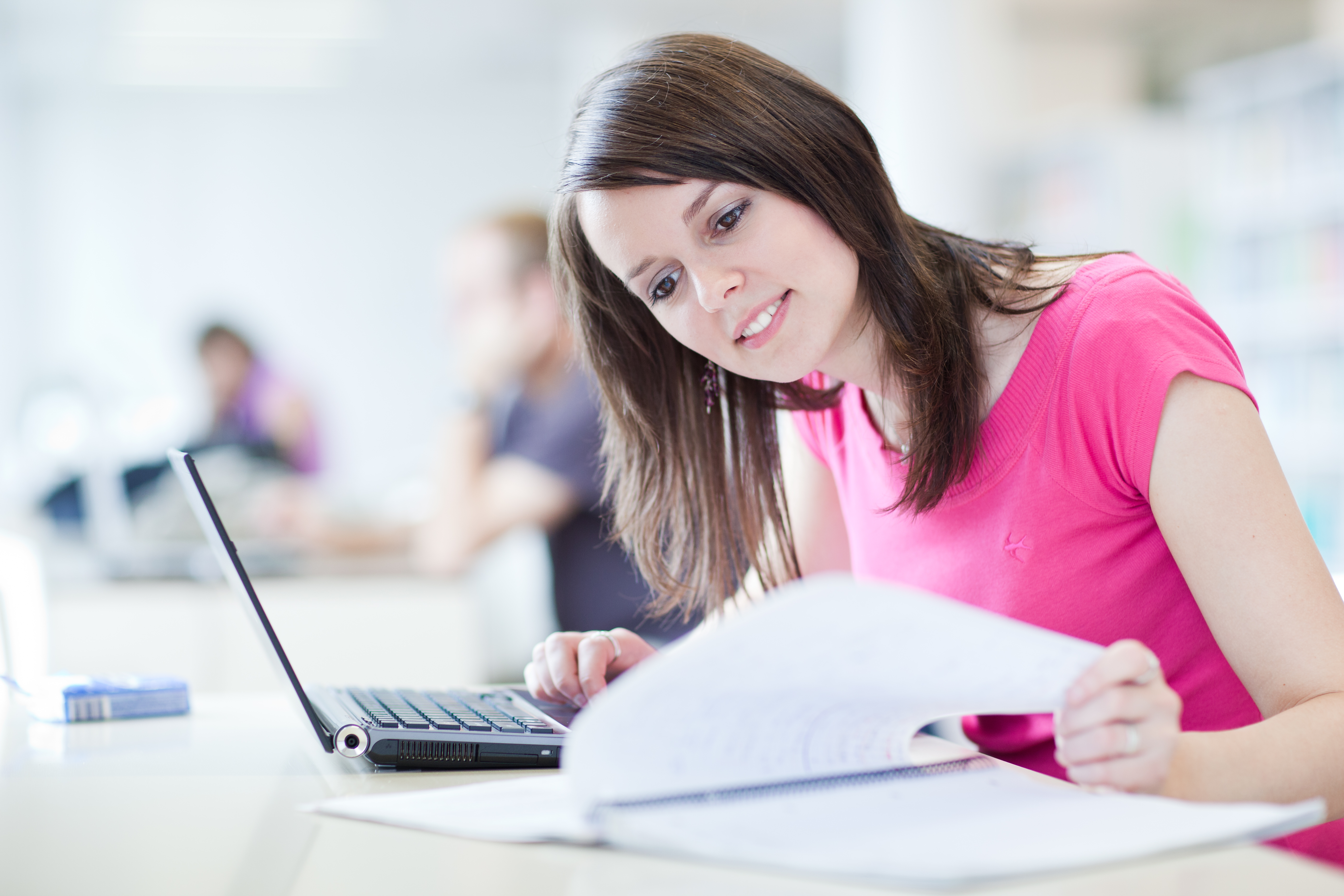 Woman in pink top studying - shutterstock_64648147
